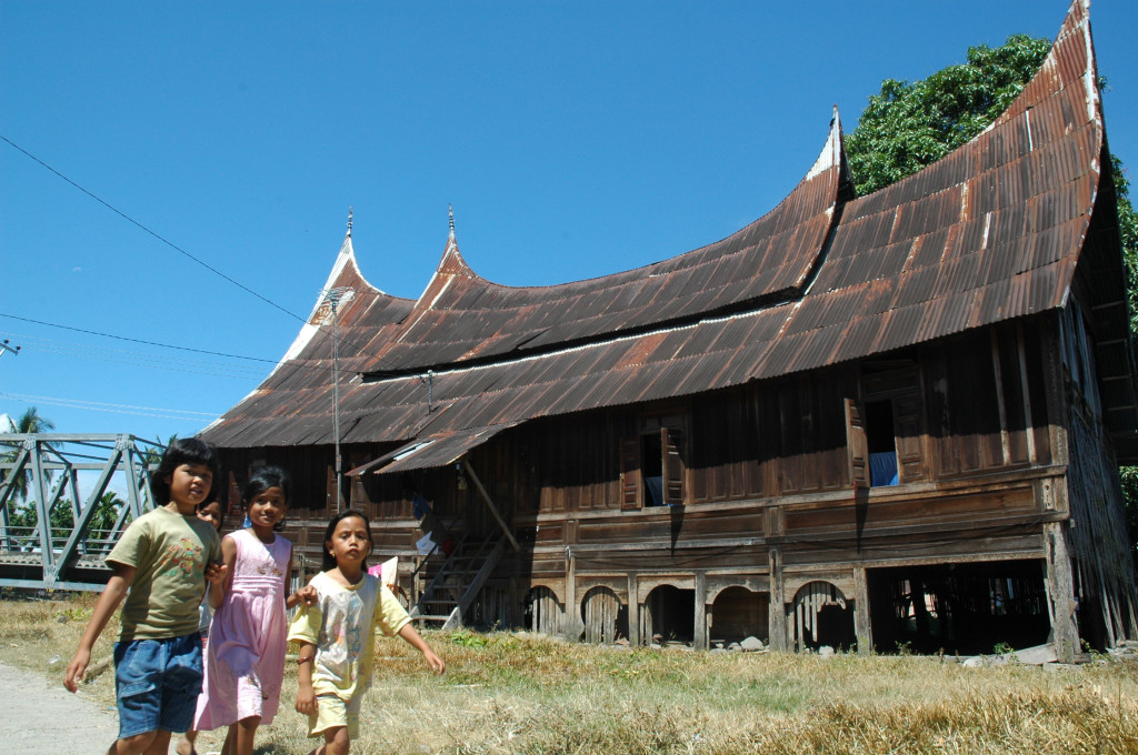 children running in front of a Padang house, Sumatra