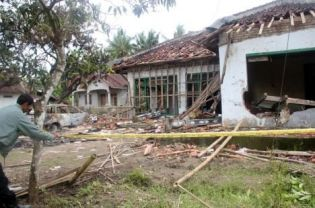 Policeman outside Ahmadiyya cleric Suparman's house after the attacks, By: Antara