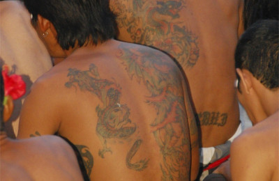 Tattooed backs at a ceremony, By: Rollan Budi
