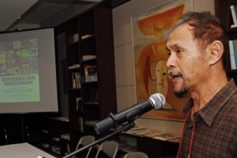 Goenawan Mohamad with in the background one of his books 'Democracy and disappointment'